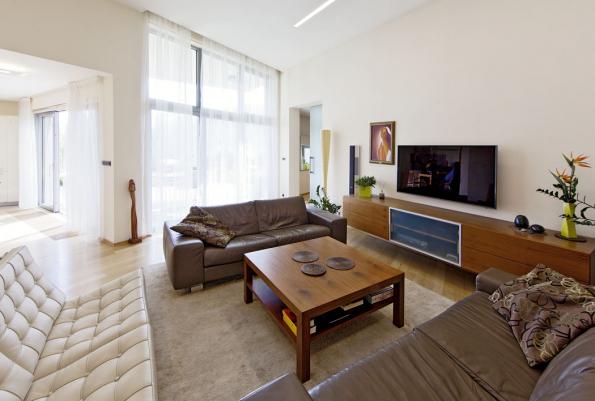 Volné průhledy opticky spojují prostor kuchyně a jídelny s obývacím pokojem a terasou. Jednotící roli hraje také lepená dřevěná podlaha, která léty jen získala na půvabu a přirozeném přírodním vzhledu.