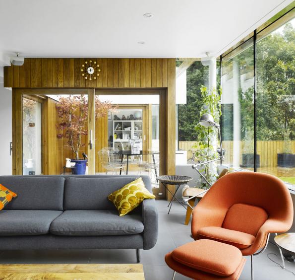 Podlaha vretro stylu může být jakákoliv, tato šedá dlažba ovšem velmi příjemně doplňuje dřevěný obklad stěny, tak typický pro 70. léta. Barva podlahy efektně graduje nasytě šedém potahu pohovky, kterou oživují barevné polštářky sretro vzorem.