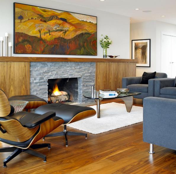 Retro atmosféru kromě obkladů ze dřeva aštípaného kamene navodily především notoricky známé nábytkové solitéry odfirmy Vitra. Olejomalba nad krbem efektně opakuje všechny barvy interiéru, přitahuje zaslouženou pozornost avytváří vizuální střed pokoje.