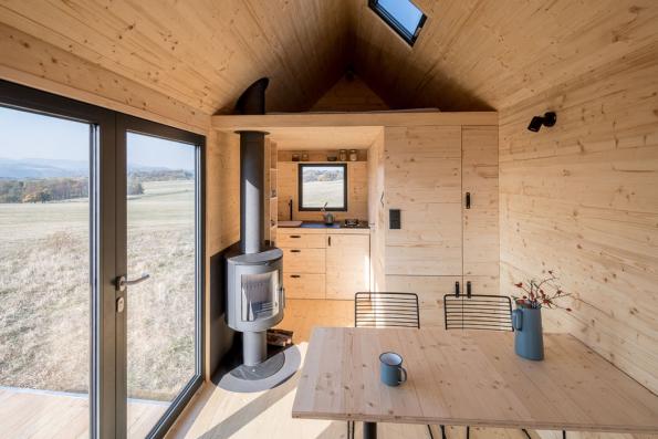 Pomocí polohování vestavěného nábytku se může přizpůsobit dispozice různým funkcím, na vyvýšeném lůžku v přízemí s dvěma řadami výsuvných šuplíků se po rozložení vyspí dva lidé a nahoře v patře nad plně vybavenou kuchyňkou je ještě manželská postel. (Zdroj: Mobile Hut)