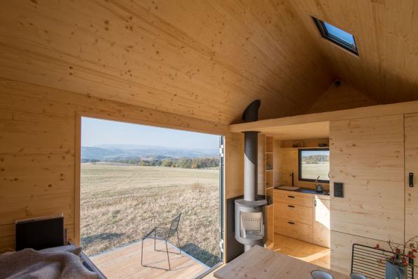 Pomocí polohování vestavěného nábytku se může přizpůsobit dispozice různým funkcím, na vyvýšeném lůžku v přízemí s dvěma řadami výsuvných šuplíků se po rozložení vyspí dva lidé (horní řada zásuvek jsou úložné prostory) a nahoře v patře nad plně vybavenou kuchyňkou je ještě manželská postel. (Zdroj: Mobile Hut)
