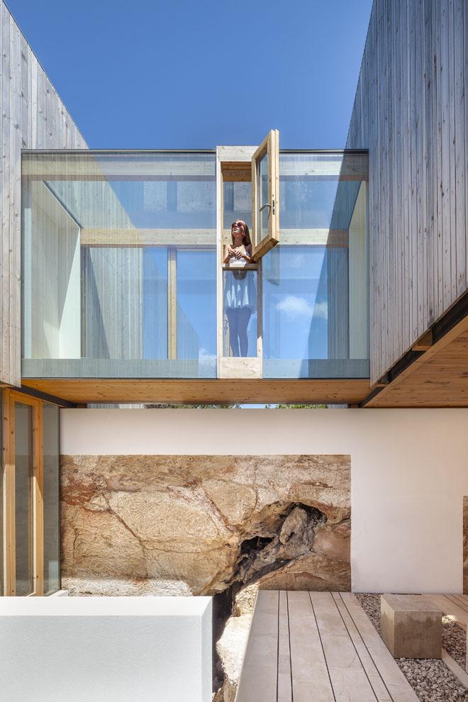 Horní podlaží domu propojují dva skleněné tubusy. Vespodním podlaží nenajdete žádné stěny, jen kámen, sklo anosné železobetonové prvky. Přirozené kamenné útvary vymleté vodou avětrem se staly originálním anedocenitelným uměleckým dílem adávají domu jasnou identitu.
