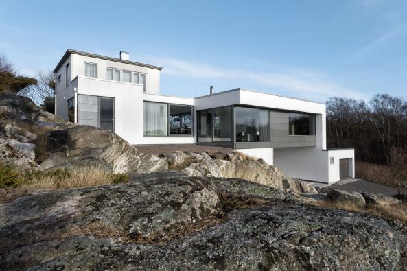 Fasáda se strukturou vertikálního bílého obkladu ahorizontálně orientovaných antracitových cementových desek krásně zapadá doreliéfu vyběleného skalního podloží.