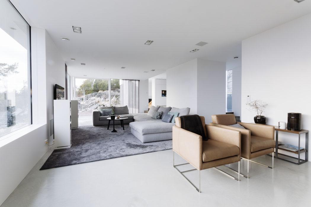 Společný obývací prostor je poměrně rozlehlý, vestavěné prvky mu dávají příjemnou členitost.  Funkční zařízení vestylu Bauhaus, jemné decentní barvy apřírodní materiály se spojují vútulný aharmonický dojem.