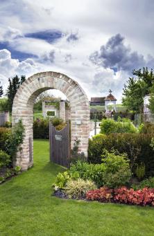 Inspiraci pro stavbu obloukového průchodu zneomítnutých cihel si majitelé přivezli zAnglie. Vytváří působivý optický předěl mezi okrasnou zahradou azáhony se zeleninou.
