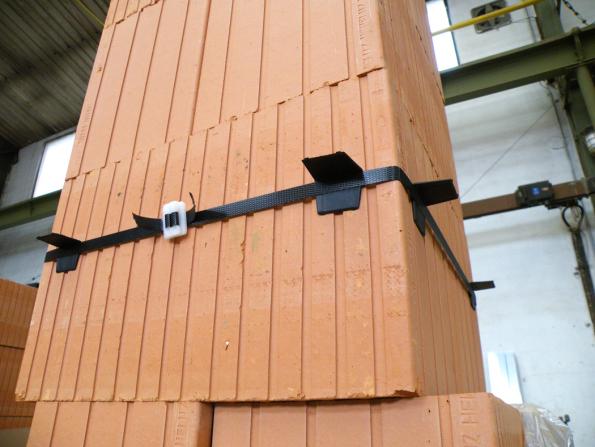 1. Do místa spodní části prostupu připevníme okolo komína pomocí plastových sponek montážní pásku. Za ni zavlékneme plastové rohy, které budou prostup držet po dobu zaschnutí tmelu. (Zdroj: HELUZ)
