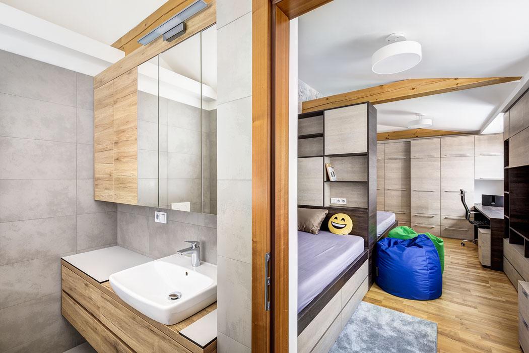 Pokoj chlapců vedruhém patře. je nábytkovou sestavou zčásti prostorově rozdělen nadvě části, aby každý znich měl soukromí naodpočinek apřípravu doškoly.