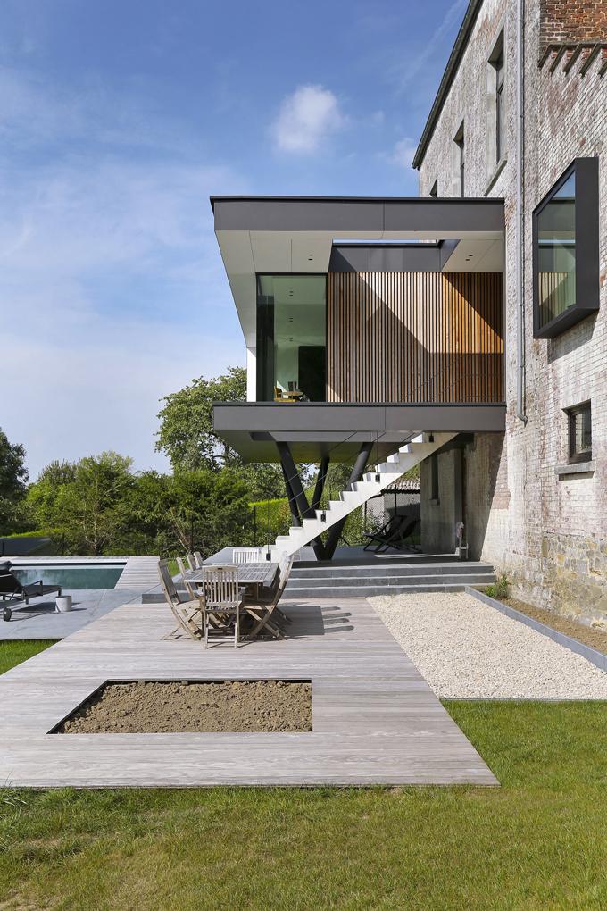 Obklad zčerných abílých cementovláknitých desek, plášť zdřevěných hranolů, ocel, beton avelkoformátové sklo identifikují moderní architekturu vkontrastu se starým zdivem. Terasa má příjemný povrch zodolného dřevoplastu, střední část je vydlážděna kamenem.