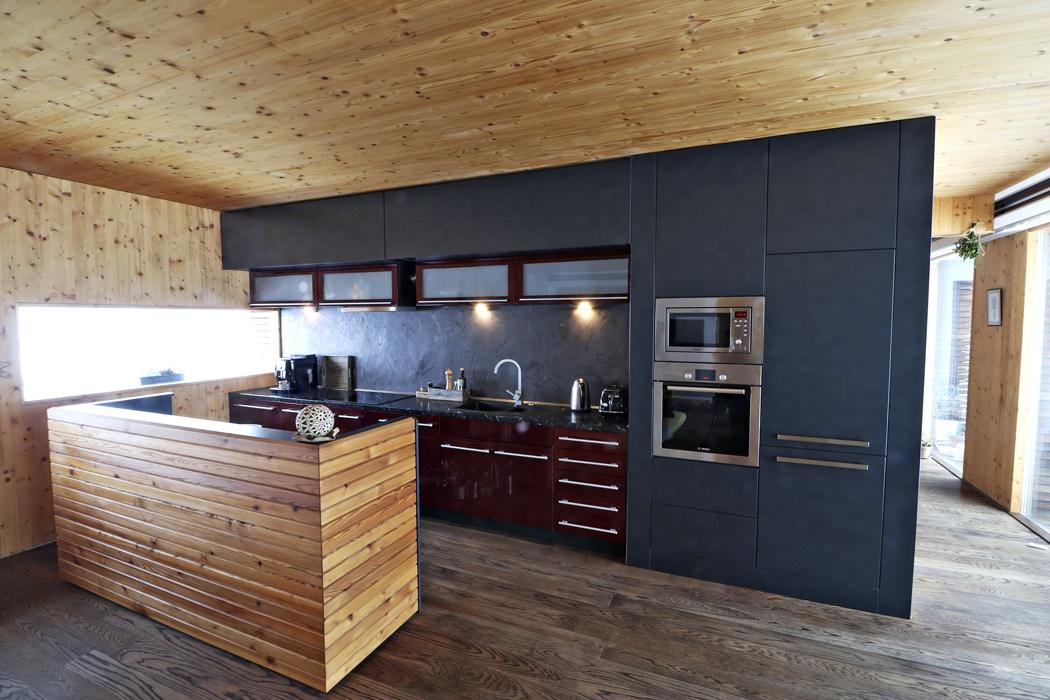 Kuchyňská linka je instalována na dělicí příčku ošetřenou stěrkou, z druhé strany je prostor kuchyně vymezen volně stojícím pultem ve tvaru písmena U.