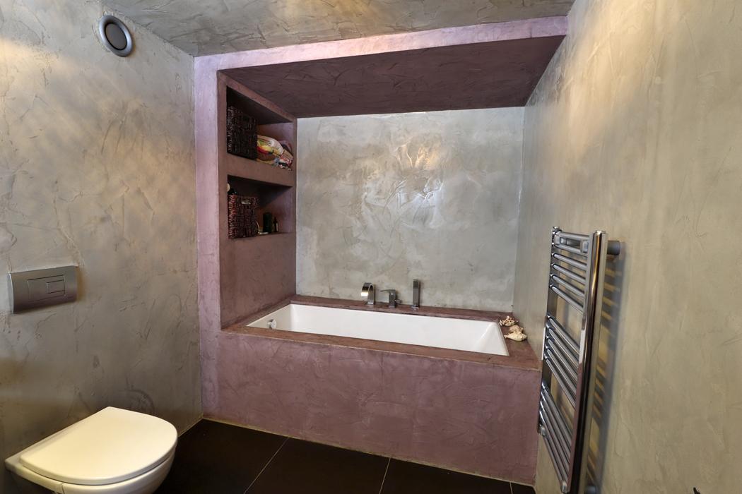 Ztvárnění stěn koupelny v syrovém naturálním pojetí odkazuje až někam ke starověkým hliněným stavbám. Vlevo pod stropem je vidět výdech domovní vzduchotechniky.