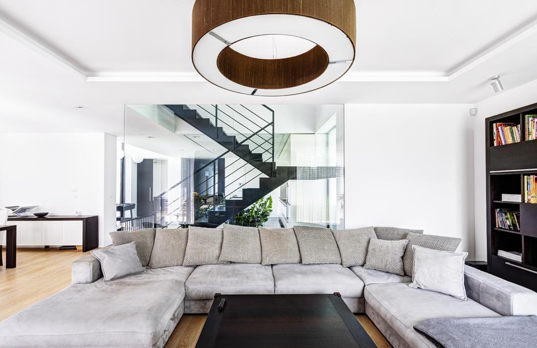 Interiéru přízemí dominuje silueta subtilního schodiště zčerně lakované oceli, umístěného volně vcentru dispozice. Obývací pokoj je vybaven sdůrazem napohodlí aútulný vzhled. Architekti sem navrhli stolek aknihovnu sdýhou wengé, které krásně vyniknou natřívrstvé dubové podlaze. Společnost jim dělá rozlehlá sedačka sdecentním šedavým čalouněním.