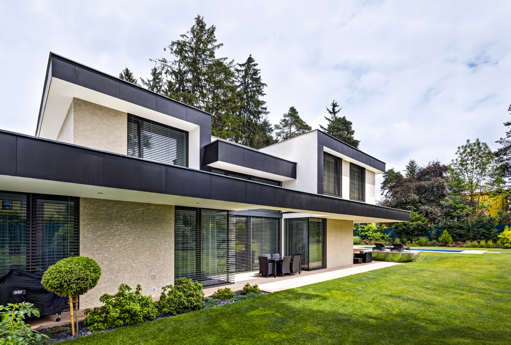 Vertikální charakter stavby zvýrazňují přesahující stropní konstrukce asvislé stěny, zvýrazněné obkladem zčerných fundermaxových desek.