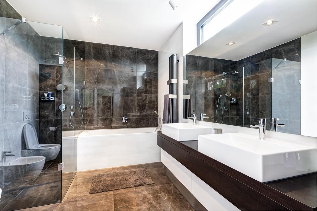 Leštěná dlažba, dýha wengé, bílá barva asklo – koupelny tvoří se zbytkem domu nedílný celek.