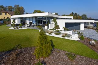 Bílá stavba krásně vynikne nazeleném trávníku adlažbě imitující omšelé dřevo. Oblázkové záhony steplomilnými rostlinami si navrhla aosázela sama majitelka