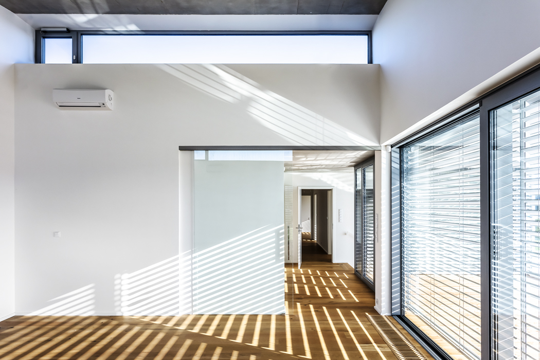 Průhled společným obývacím prostorem s čtyři metry vysokým stropem. Společným jmenovatelem obytných místností jsou vyhřívané dubové podlahy, na nichž, stejně jako na stěnách, slunce vykresluje linie žaluzií.