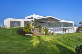 Dům se celoprosklenou jižní fasádou otevírá dozahrady, jejíž modelace pouze zvýraznila přirozený profil terénu včetně solitérních kamenů pocházejících znedalekého okolí.
