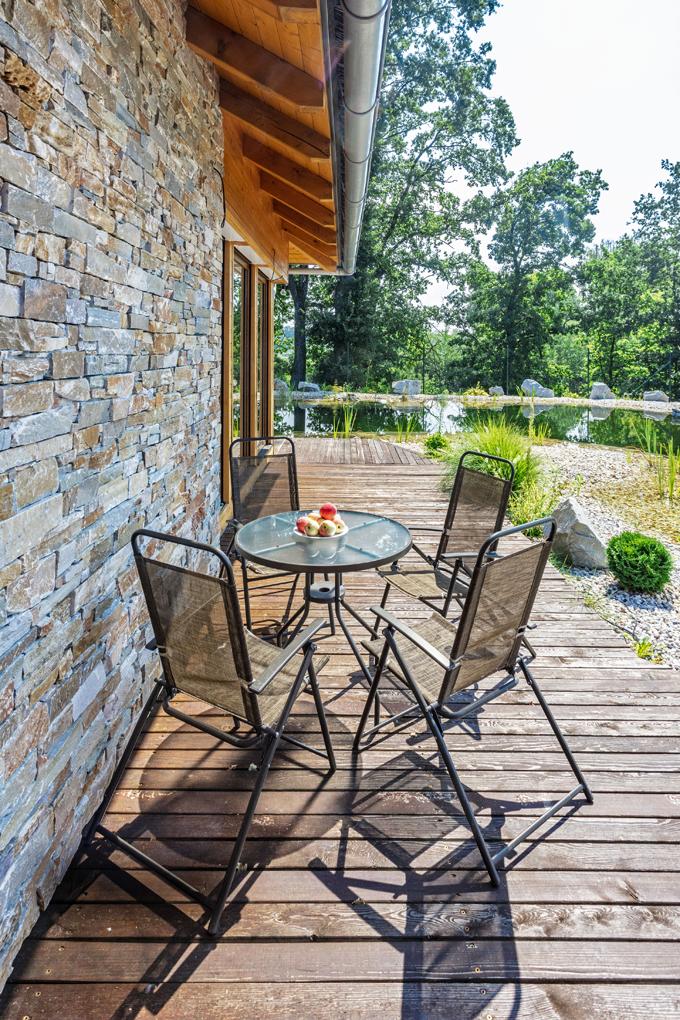 Fasáda domu je ze sukovatých prken sibiřského modřínu doplněných o pásy kvarcitového kamene. Dřevěná terasa propojuje obývací pokoj s hlavním vchodem a ložnicí.