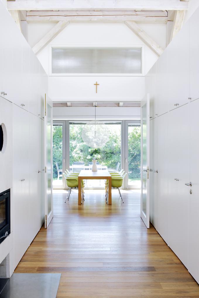 Minimalismus abílá barva povýšily halu naelegantní prostor. Dvoukřídlými dveřmi lze vejít dospolečného obytného prostoru aodtud opět naprotější straně francouzským oknem naterasu. Otevřením obou dveří se opticky iskutečně zvětšuje vnitřní obytný prostor domu.