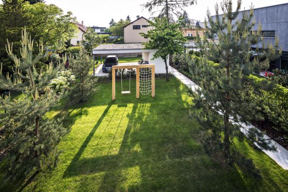 Pohled nahlavní pobytový prostor mezi domem apřístřeškem pro auta sdominantními borovicemi.