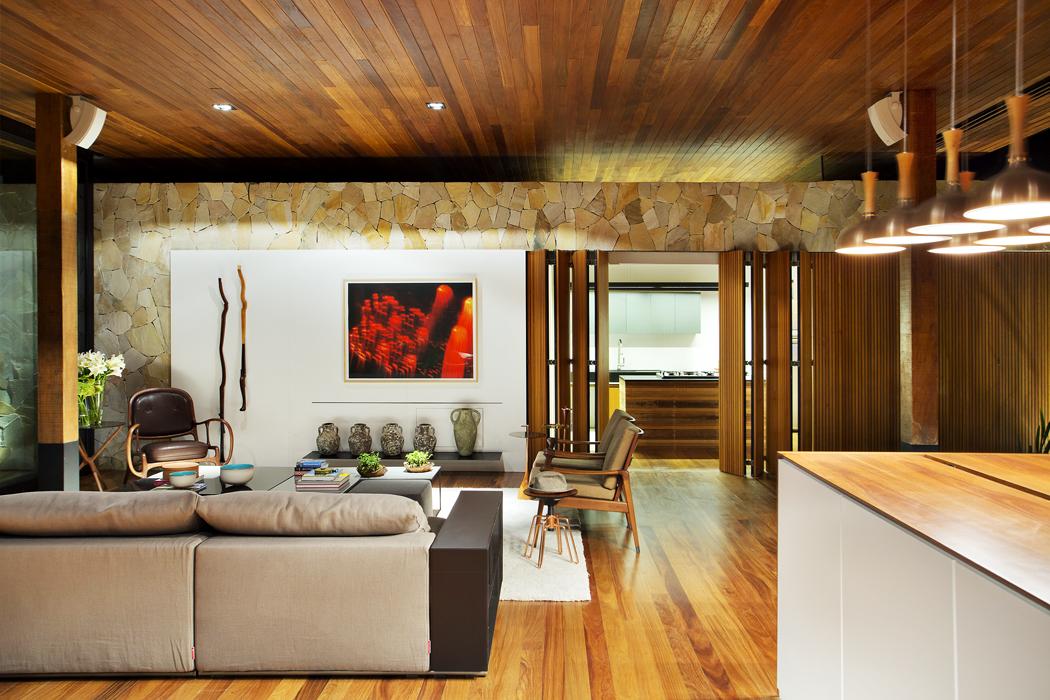 Kuchyň je odspolečného obývacího prostoru oddělena panelovou skládací stěnou zdřevěných profilů. Stejné panely stíní okna také vložnicové části domu. Vybavení interiéru navrhl architekt Tici Adriani vkosmopolitním stylu tak, aby působil útulným dojem. Společným cílem bylo harmonicky propojit moderní architekturu sprostředím tropické zahrady.