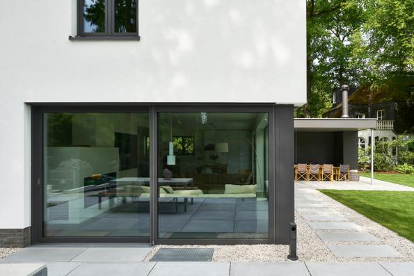 Přechod mezi zahradou a domem tvoří betonové desky a rýnský štěrkopísek. Tmavé rámové profily prosklených ploch kontrastují se světlými povrchy. (Zdroj: Schüco CZ, foto: Christian Eblenkamp)