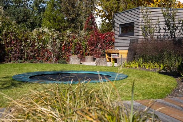 Kout zahrady sdomkem Naturhouse, okolo terasy ze sibiřského modřínu auprostřed trampolína, která má schovanou konstrukci pod úrovní terénu.