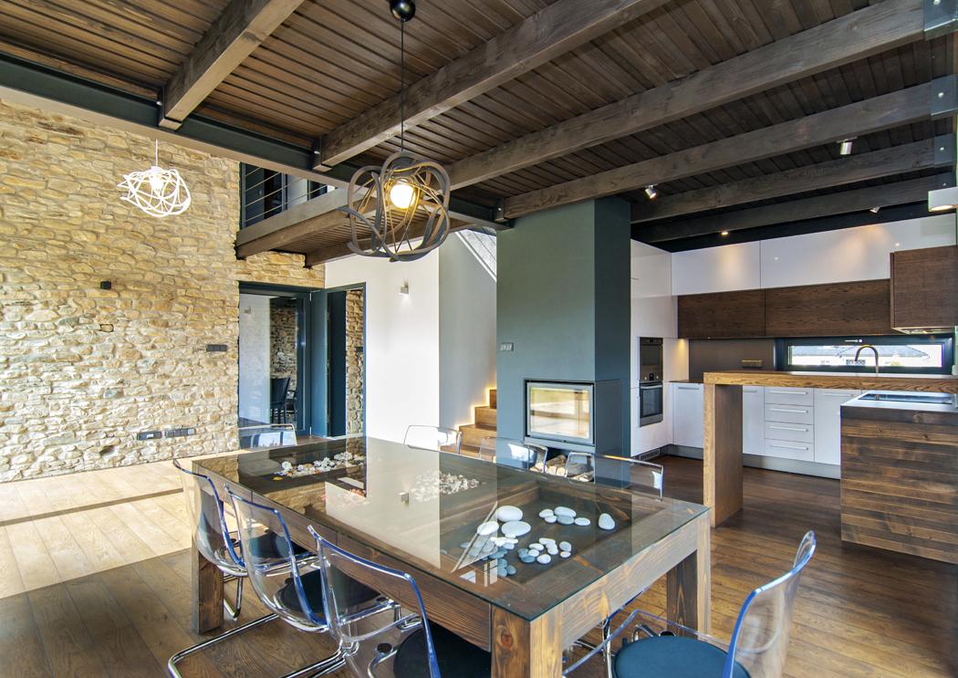 Interiér výběrem materiálu i barevností koresponduje s exteriérem. Převládají odstíny přírodního dřeva doplněné antracitovými nátěry kovových prvků a krbového tělesa. Většinu vybavení tvoří originály vyrobené podle návrhu architekta, například jídelní stůl ze stropních trámů.