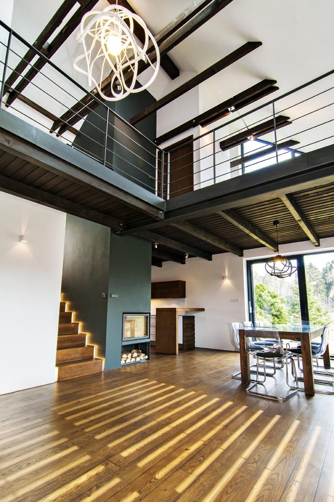 Vnitřní uspořádání je zcela moderní. Dřevěný trámový strop agalerie nad společnou obývací částí jako by se volně vznášely vprostoru. Střešními okny ioknem veštítě sem proniká hodně světla.