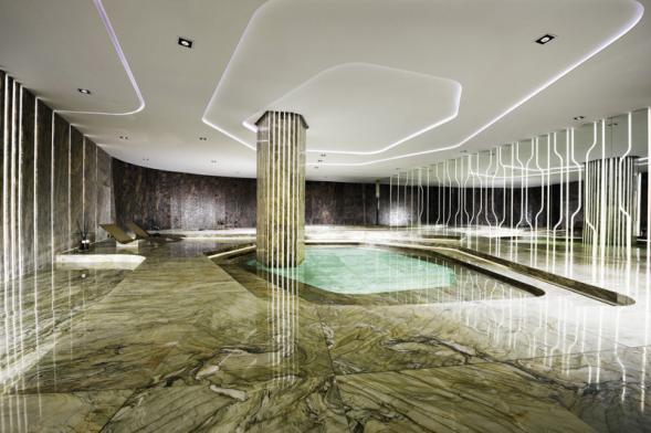 Vnitřní bazén aspa, obložený leštěným amatným kamenem vetřech zemitých barevných odstínech azvýrazněný dynamickými liniemi integrovaného osvětlení, symbolizuje střet energie země avody.  Unikátní projekt navrhl architekt Alessandro La Spada, realizovala společnost Antolini.