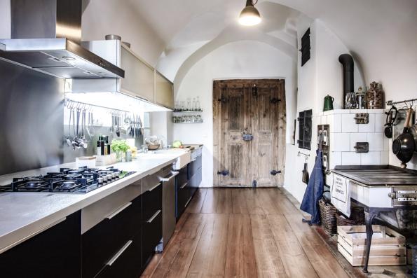 Pod historickou valenou klenbou avedle nádherných zrenovovaných starých dveří stojí moderní high-tech kuchyňská linka.