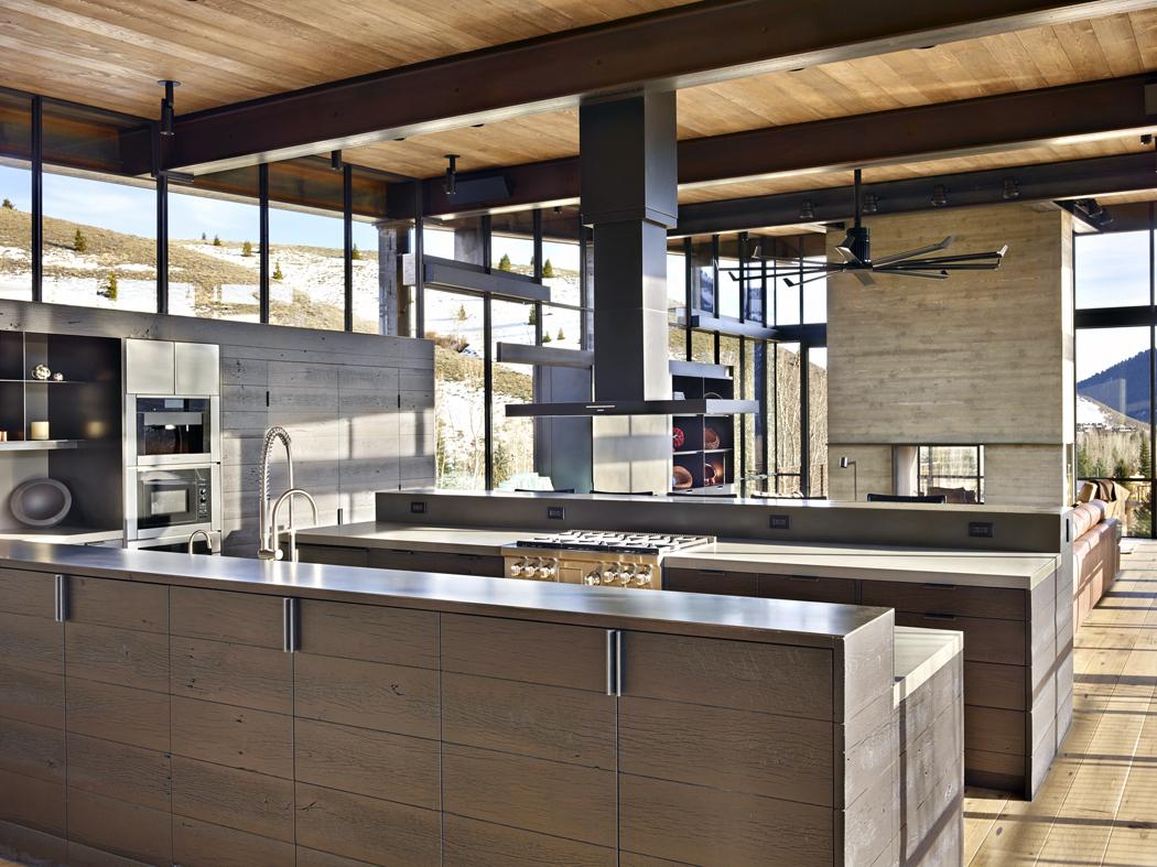 Také nábytek adalší vybavení interiéru charakterizuje mocný industriální výraz. Například dřevěná kuchyňská dvířka shrubou strukturou ašedým nátěrem dokonale imitují litou betonovou stěnu, najejíž povrch se otiskla struktura dřevěného bednění.