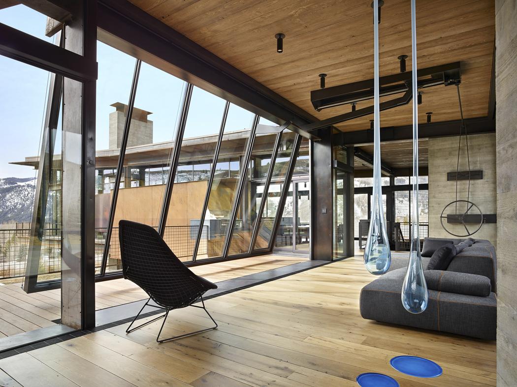"""Spojovací """"můstek"""" mezi dvěma křídly domu lze zčásti nebo zcela otevřít pomocí speciální nazakázku navržené výklopné skleněné stěny. Je propojena smasivním pojezdem nastropě aovládacím kolem nastěně."""