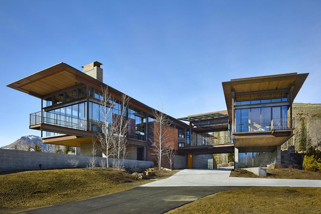 """Architektonický výraz domu určuje pohledový beton, viditelné masivní ocelové nosníky asklo. Extrémní přesah druhého podlaží dovolného prostoru ještě prodlužují vyhlídkové ocelové lávky, které jsou """"volným pokračováním"""" nosné železobetonové desky."""