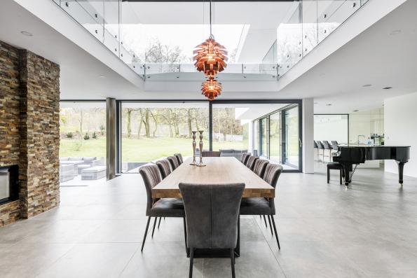 Dominantní úlohu společného jídelního stolu vrodinné vile zvýrazňuje otevření stropu nahoru nagalerii. Díky proskleným stěnám vobou podlažích má celá rozlehlá dispozice světlo avzdušnou atmosféru (design afoto ateliér Kareš-Rais)