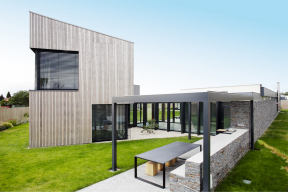 Termowoodem obložený hostinský domek je na rozdíl od zbytku staveb dvojpodlažní. Grilovací kout využívá andezitem obloženou zeď, která zde ve snížené formě slouží jako lavice.