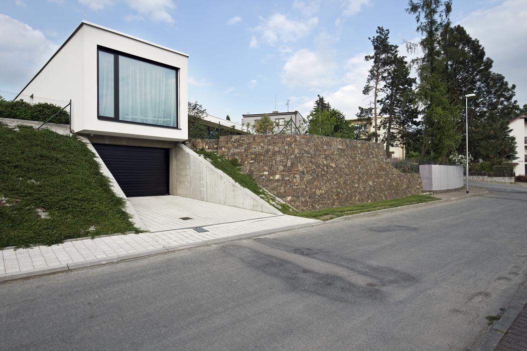 Vjezd do garáže s přečnívající hmotou ložnice, po straně s gabionem, který vytváří přidanou hodnotu pro zatravněnou zahradu, jenž spoluvytváří hlavní myšlenku celého konceptu rodinného domu.