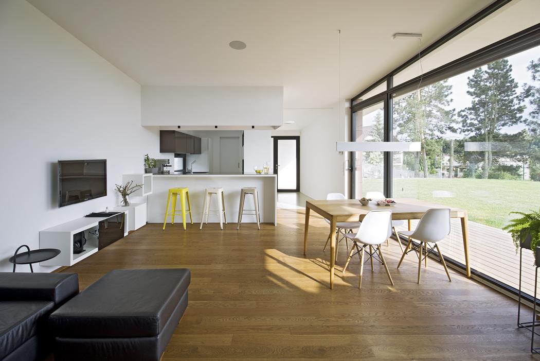Součástí obývacího pokoje je vnitřní a venkovní jídelna s bezbariérovým vstupem na terasu. Hlavním motivem interiéru je jemně rustikální dub s upozaděným bílým designem.
