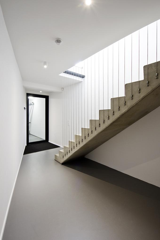 Betonové schodiště je odlito z jednoho kusu, zábradlí tvoří napnutá ocelová lanka. Šedobílý bezespárý povrch betonu vnáší do prostoru jistou osobitost a stabilitu.