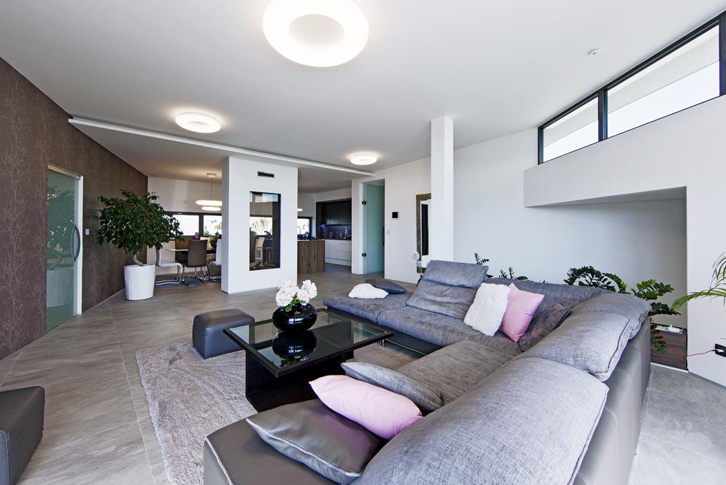Společný obývací prostor sahá odjižní fasády kseverní, kde je umístěna kuchyň ajídelna, skrytá zavelkým proskleným plynovým krbem. Vinteriéru převládají zemité  přírodní barvy amateriály. Velkoformátová keramická dlažba dokonale imituje šedý kámen akontrastuje shnědou tapetou sdekorem větví.
