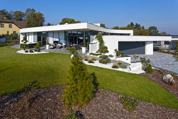 Bílá stavba krásně vynikne nazeleném trávníku adlažbě imitující omšelé dřevo. Oblázkové záhony steplomilnými rostlinami si navrhla aosázela sama majitelka.
