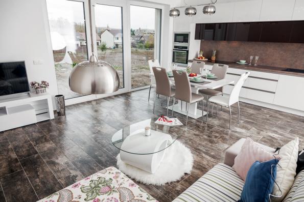 Obývací pokoj má tři zóny – kuchyňskou, jídelní aobývací. Francouzské okno vede naterasu. Vpřízemí je nazemi položena dlažba, vpatře je podlaha Hydrocork vestejném designu.