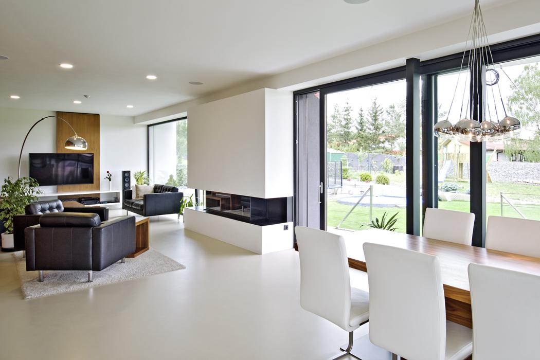 Široké prosklené posuvné plochy bezbariérově propojují společný obývací prostor skrytou terasou.