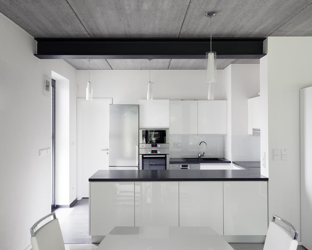 Kuchyně je vneutrální nadčasové bílé barvě, kontrastující sčernou pracovní deskou.