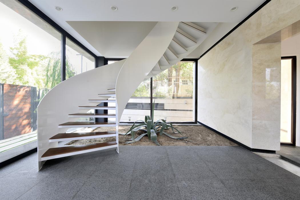Staticky náročná samonosná konstrukce bílého schodiště s dřevěnými prvky je malým uměleckým dílem.