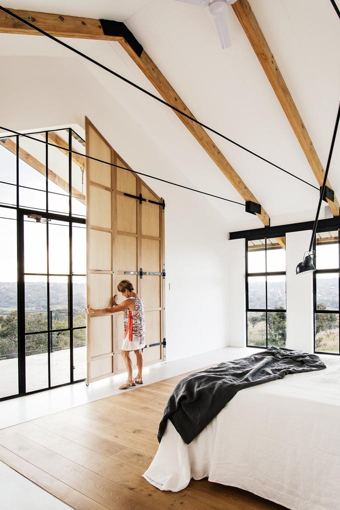Hlavní ložnice nabízí impozantní výhled dokrajiny. Vnitřní dřevěné okenice umožňují zastínit prosklený šít azabraňují jak přehřívání, tak únikům tepla.
