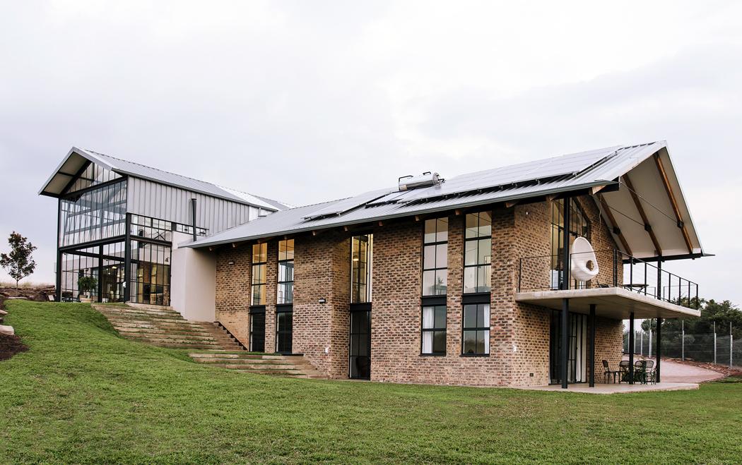 Kombinace režných cihel, ocelových tabulkových oken abetonu stavbě propůjčuje vzhled starého industriálního objektu nebo zrekonstruované stodoly. Vpravo je vidět ložnice svelkým betonovým balkonem, krytým výrazně přesahující střechou.