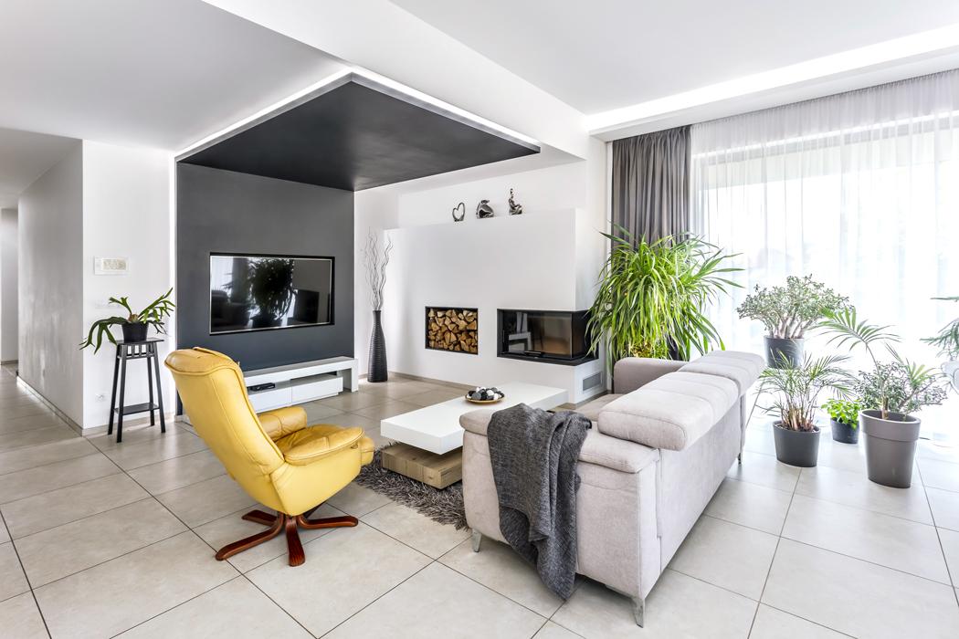 Vlevé části snímku je vidět otevření společného obývacího prostoru dochodby. Sádrokartonové podhledy umožnily zajímavé atypické instalace, například krbovou desku lemovanou integrovaným LED osvětlením.