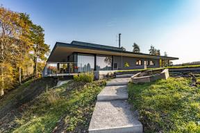 Těžiště domu je orientováno dozadní části pozemku, který spadá směrem krybníčku. Poobvodě stavbu lemuje přesahující střecha, která zvýrazňuje její horizontální ráz ataké účinně stíní prosklené plochy.