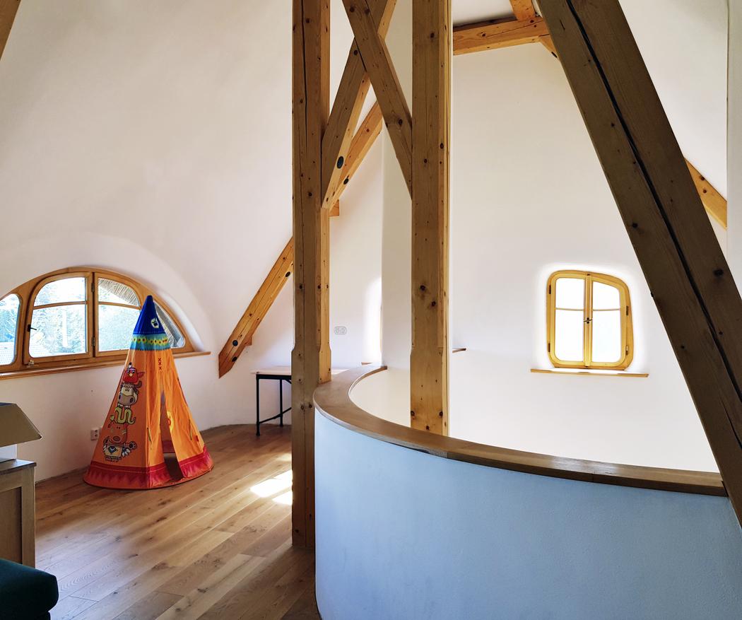 Pohled docentrální haly vprvním patře. Vpravo je otevřený prostor nad pecí, kudy stoupá teplý vzduch, proniká tudy isvětlo dopřízemí.