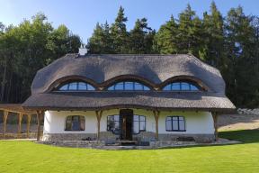 Jižní fasáda svelkými okny doobytných místností. Přesah střechy zajišťuje, aby se dům vlétě nepřehříval, avpřízemí vytváří prostor pro posezení.